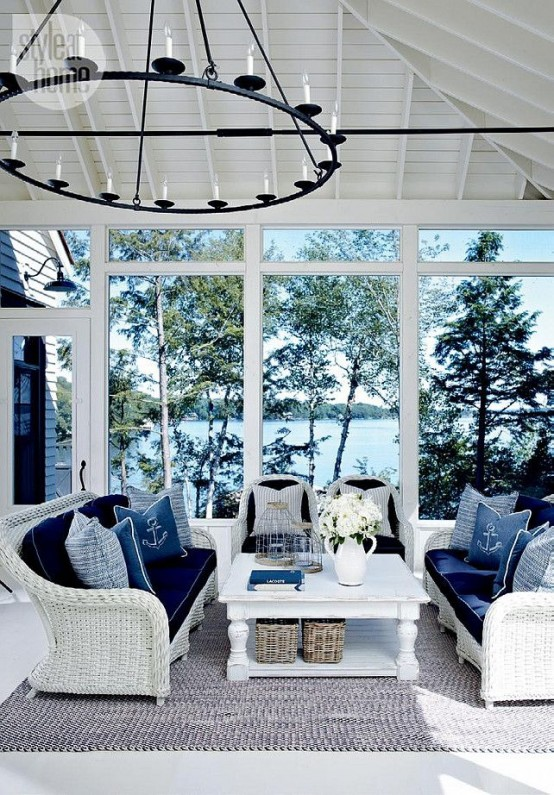 a stylish nautical sunroom with white wicker furniture, navy upholstery and pillows and a vintage chandelier