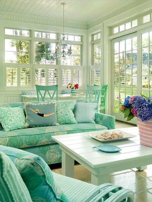 a tiffany blue coastal sunroom with a dining and living room space, with blooms and printed upholstery