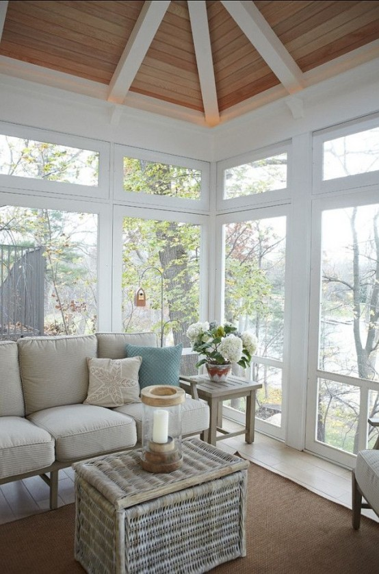 a beach sunroom nook with a blue and neutral L-shaped bench and comfy cushions and pillows is lovely