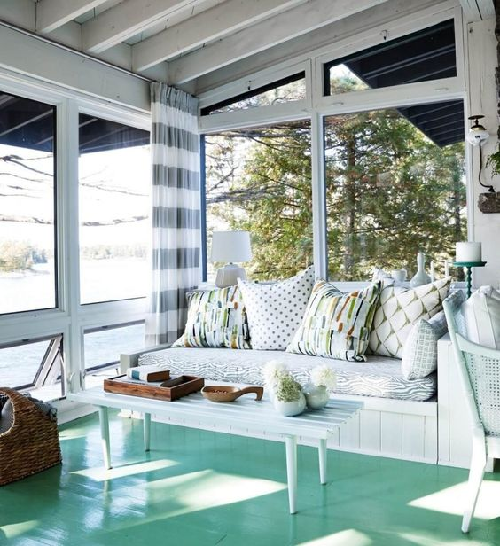 a stylish beach sunroom with an aqua floor, white wooden furniture and printed textiles