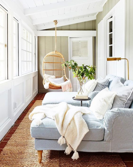 a modern coastal sunroom with striped daybeds, white pillows and blankets, a hanging rattan chair and greenery