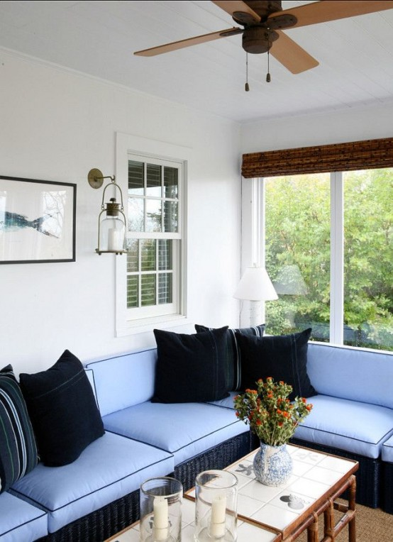 a modern beachy sunroom with a blue L-shaped sofa, black pillows, wooden tables and candles and art