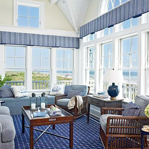a nautical sunroom with a blue carpet, blue curtains, vintage wood furniture with blue upholstery and a gorgeous view
