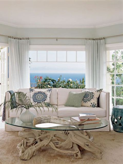 a beach sunroom with a modern neutral sofa, a driftwood and glass table and printed pillows and light green curtains