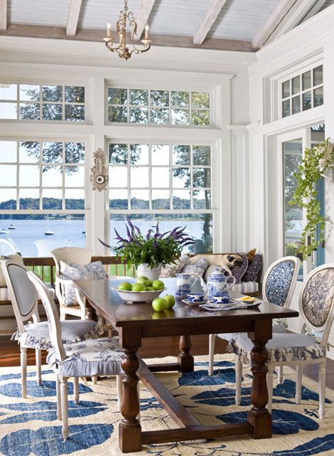 a vintage beach sunroom with a wooden table, blue and white printed chairs with covers, a rug and vintage chandeliers