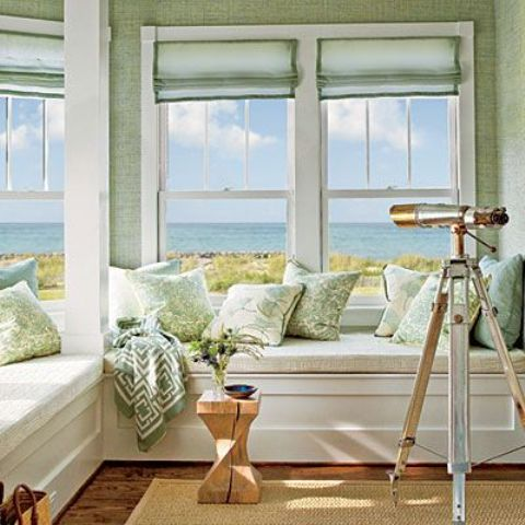 a coastal sunroom with a built-in L-shaped bench with storage, light green walls, curtains and pillows