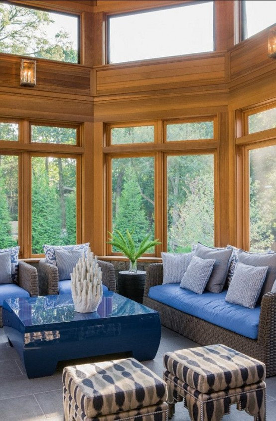 a bold blue beachy sunroom with dark woven furniture and blue upholstery, a blue table and corals plus printed stools