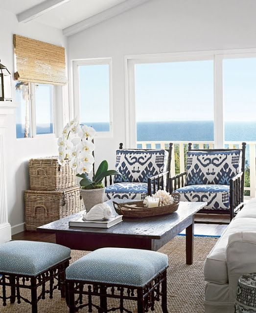 a vintage rustic coastal sunroom with dark wooden furniture with blue upholstery, baskets, shades and a white sofa plus a cool view