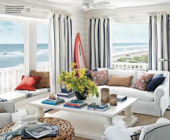a modern beach sunroom with striped curtains, elegant white furniture, a woven ottoman and red touches