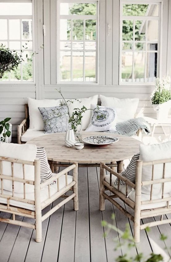 a coastal Nordic sunroom with simple wooden furniture, white and light blue pillows, greenery and elegant vases