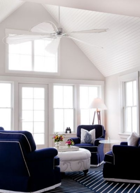 a vintage nautical sunroom with navy carpet floors, navy furniture,a white table and much natural light