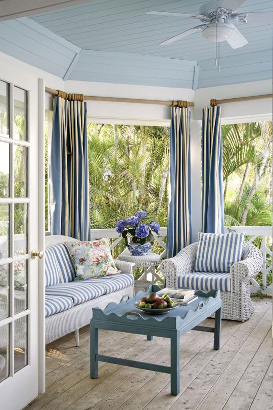 a beach sunroom with white wicker furniture and blue striped upholstery plus a vintage blue table and blue curtains