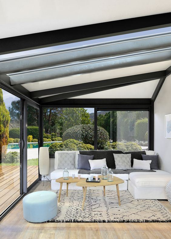 a contemporary sunroom with a sectional, some rugs, tables and ottomans and much shunshine