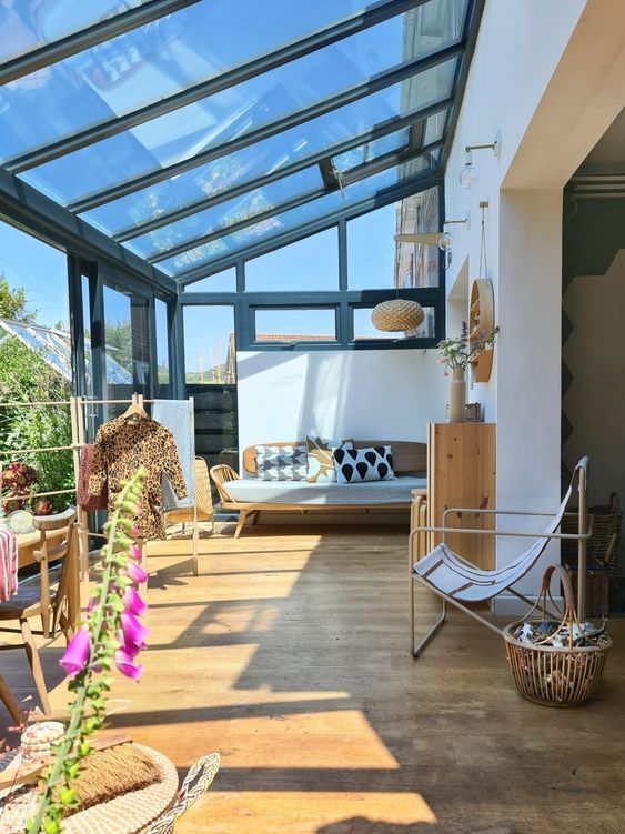 a mid-century modern sunroom with plywood and metal furniture, printed textiles and a dining space in the sun