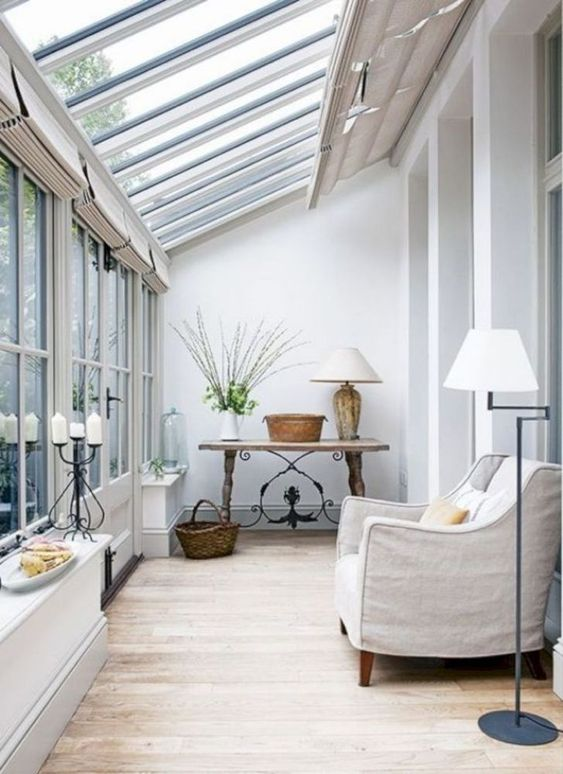 a chic vintage sunroom space with a neutral chair, a wooden table and some elegant lamps
