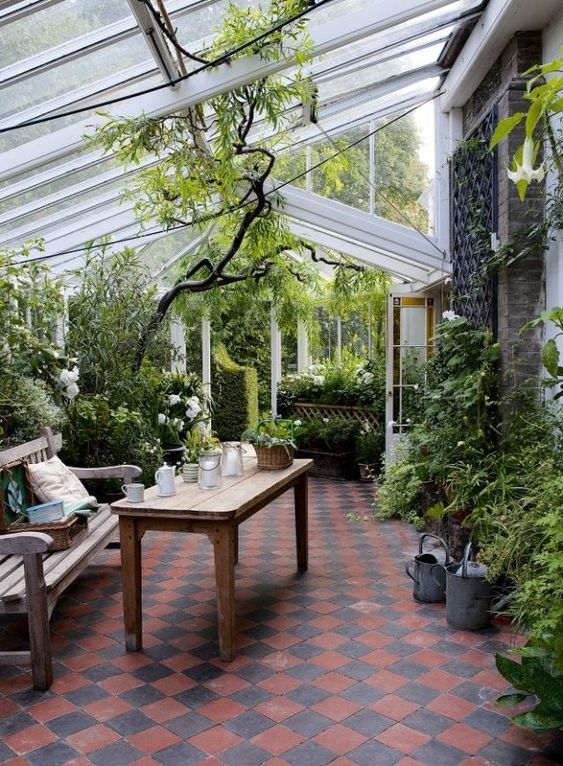 a conservatory with lots of greenery and blooms, wooden furniture and candle lanterns