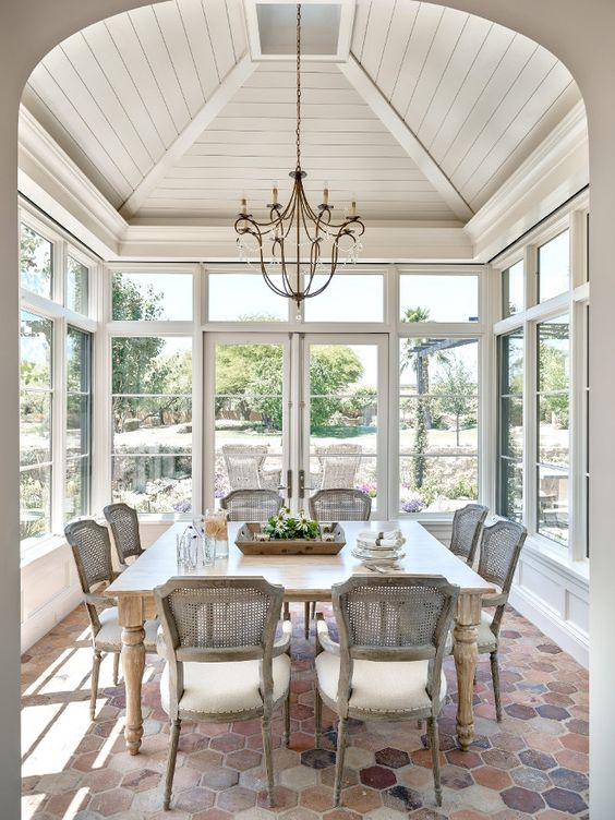 an elegant shabby chic sunroom dining space with stylish rattan chairs and a large table is great