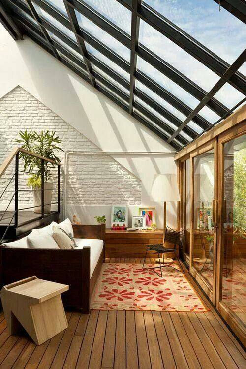 a bright modern sunroom with modern furniture, a pritned rug, potted trees and greenery and bright artworks