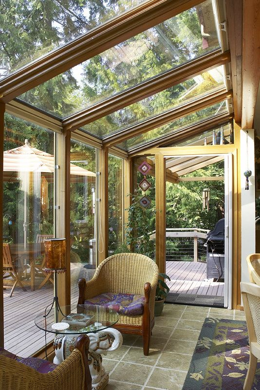 a refined vintage sunroom with rattan chairs, a glass table and a lamp is opened to the terrace