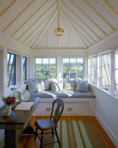 a small attic sunroom with a built-in daybed with storage, lots of pillows, a desk and a vintage chair plus a striped rug