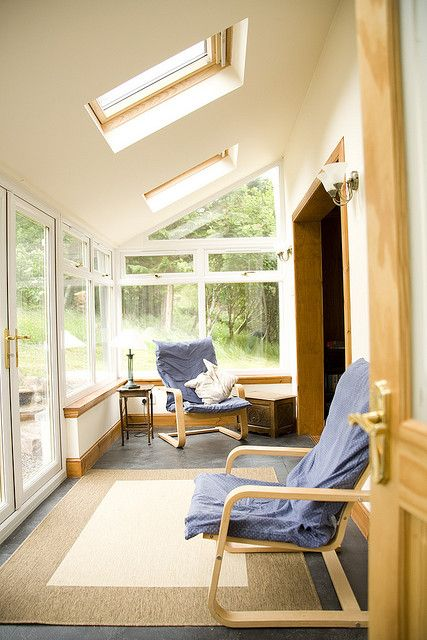 a neutral ultra-modern sunroom space with layered rugs, blue chairs and cool skylights to get more natural light