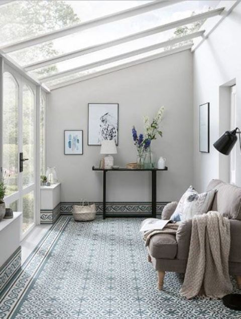 a neutral and peaceful sunroom with a tiled floor and chic furniture plus stylish artworks