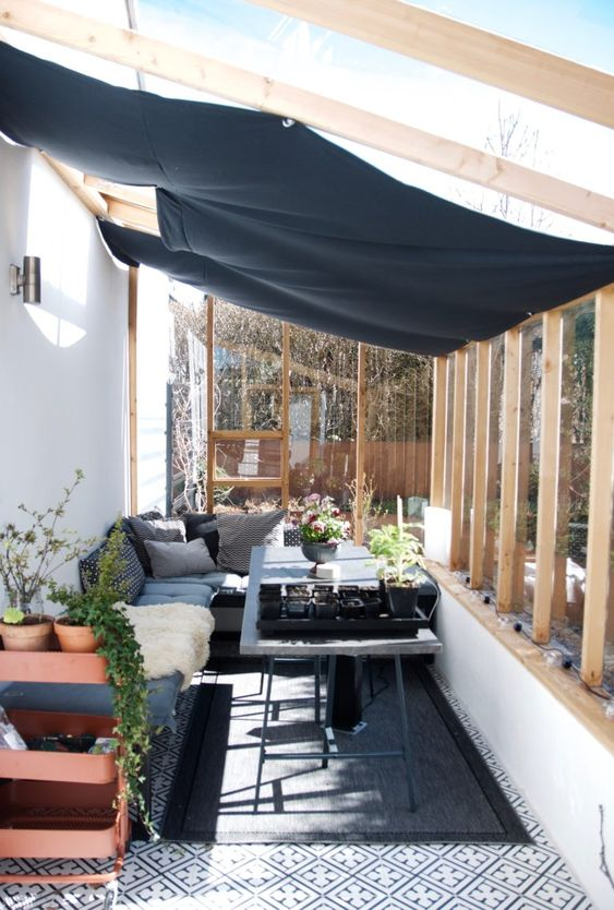 a Scandinavian sunroom, with concrete and metal furniture, potted greenery and plants and a cover to avoid excessive sunshine