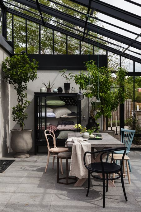 a Scandinavian sunroom with mismatching chairs, a wooden table and a large storage unit, potted greenery