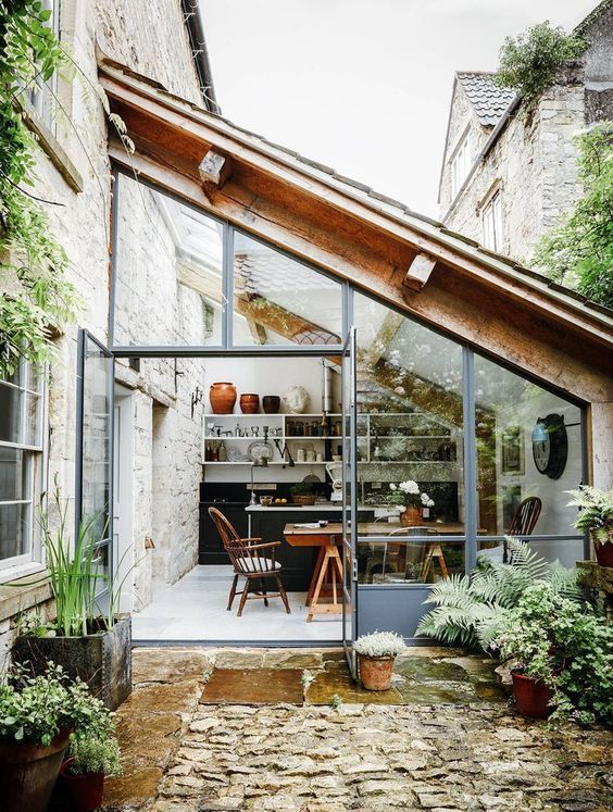 a modern kitchen and dining space designed as a sunroom are great for cooking and having meals feeling almost outdoors