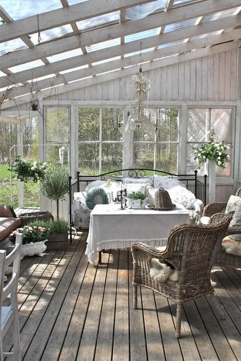 an elegant shabby chic sunroom with rattan chairs, a forged bed, potted greenery and blooms