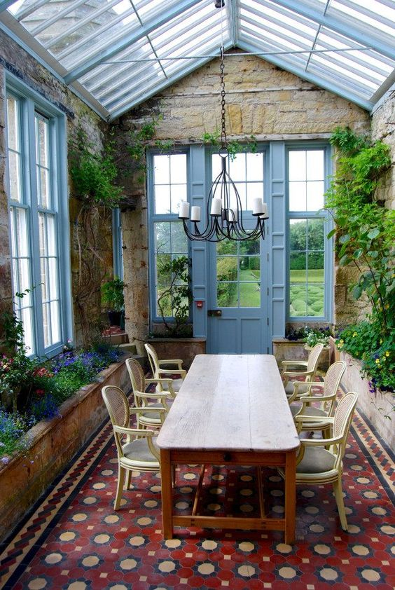 a vintage sunroom with a large carpet, a wooden table and refined chairs, potted greenery and blooms
