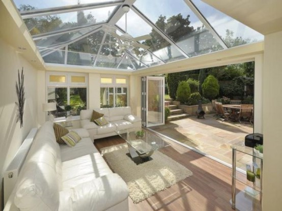 a neutral contemporary attic sunroom with stylish white furniture and glass tables and a glazed ceiling and a wall