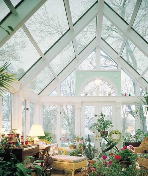 a refined and chic sunroom with a piano, rattan furniture, lots of potted blooms and greenery and lamps