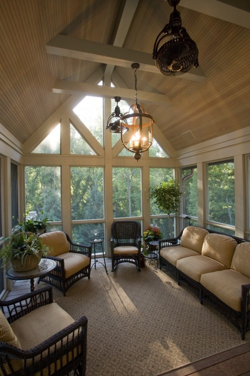 a vintage-inspired sunroom done in tan and beige, dark rattan furniture and pendant lamps and chandeliers