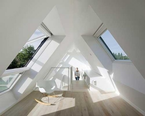 a minimalist white attic sunroom with a simple chair is an ideal space for reading or for kids' playing