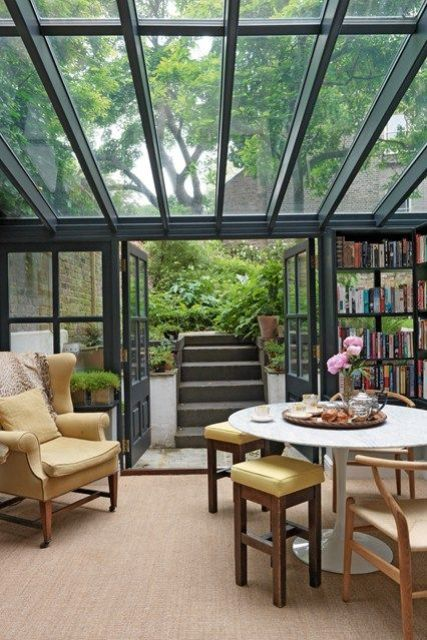 a stylish mid-century modern sunroom with simple and elegant furniture, bookshelves and a glazed ceiling and walls