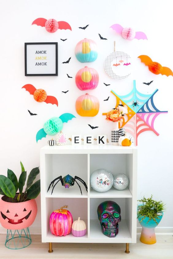 super bright and fun Halloween styling with color block half pumpkins, a bright spiderweb, pompom bats and plants