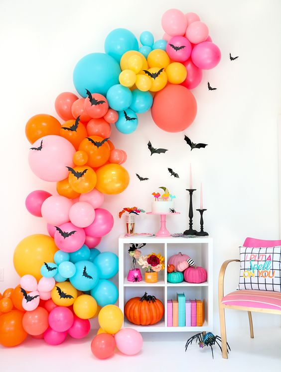 an oversized colorful balloon garland with bats, bright books and pumpkins for Halloween decor