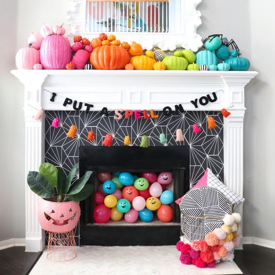 rainbow pumpkins, colorful balloons, bright tassle ghosts and a garland for Halloween