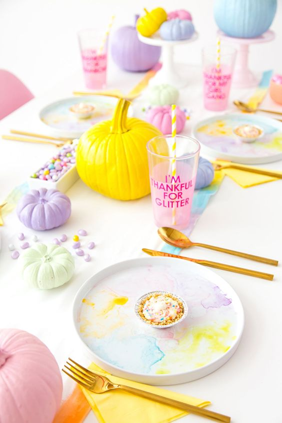 a super bold pastel Halloween tablescape with watercolor plates, pumpkins, drinks and candies
