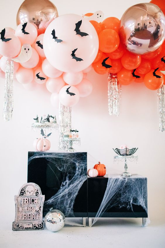 blush and orange balloons with bats, matching pumpkins and silver fringe plus spiderwebs and a gravestone