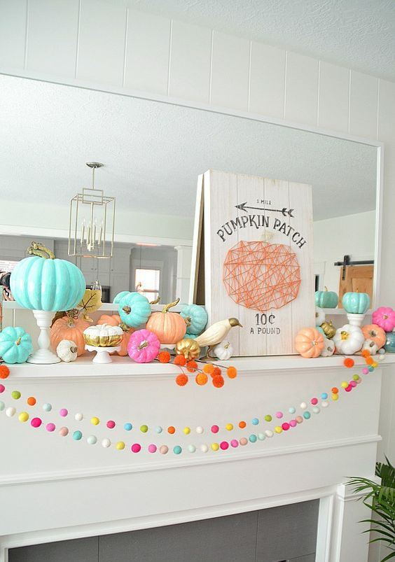 a Halloween mantel with bright felt garlands, colorful pumpkins and pompoms and a yarn sign