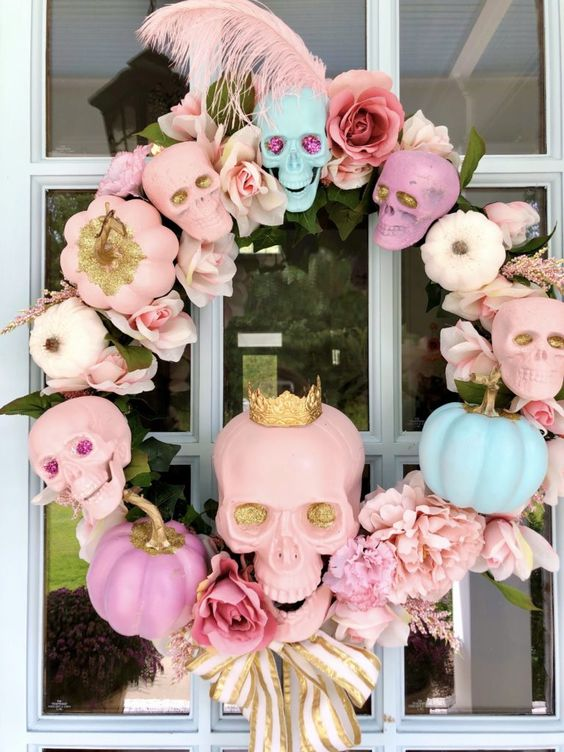 a lovely pastel skull, pumpkin and bloom wreath with feathers, ribbon bows and leaves for Halloween