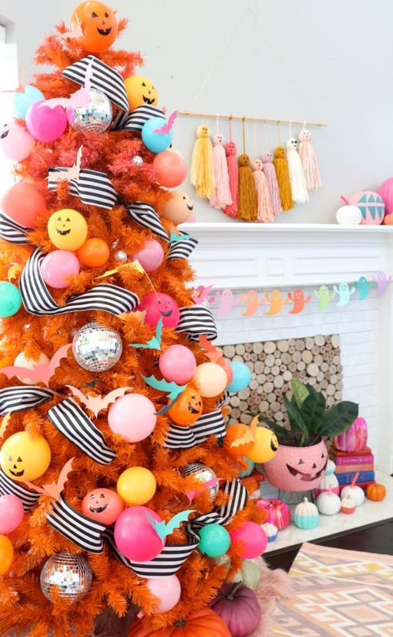 a colorful Halloween tree in orange, with pastel ornaments and balloons, striped garlands and jack-o-lanterns