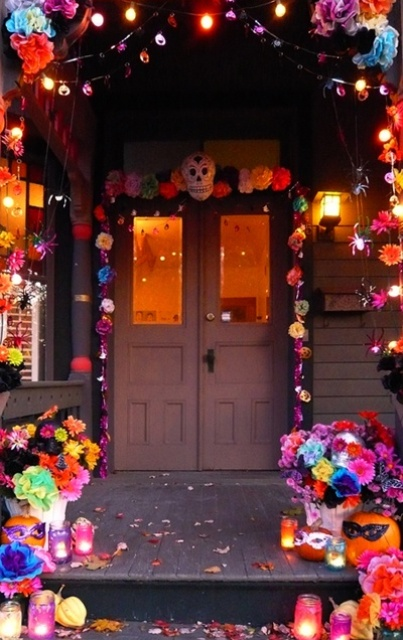 colorful Day of the Dead entrance styling with bold paper blooms, pompoms, spiders, skulls and colorful candle lanterns