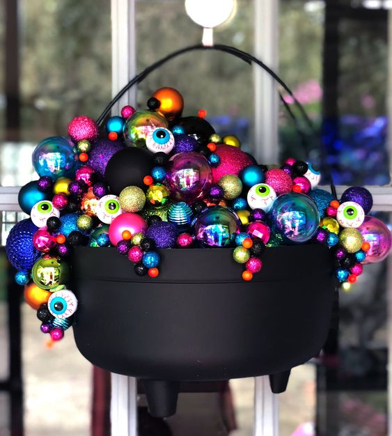 a cauldron with lots of bright and gltiter ornaments and eyeballs is a gorgeous Halloween decoration