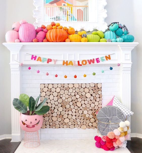 a bright Halloween mantel with bold rainbow pumpkins, a mini pumpkin garland, yarn letters and a pompom basket