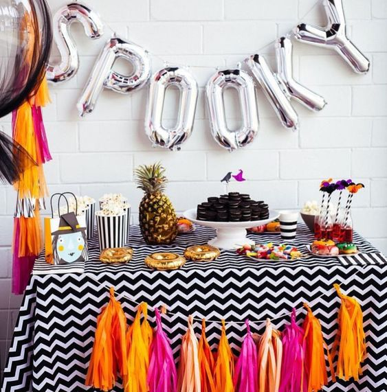 a colorful candy bar with a bright tassel garland and silver letter balloons plus a pineapple for a tropical feel