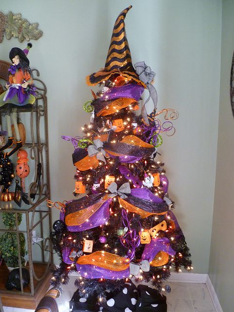 a black Halloween tree decorated with purple and orange ribbons, lights, wooden ornaments and a witch hat on top