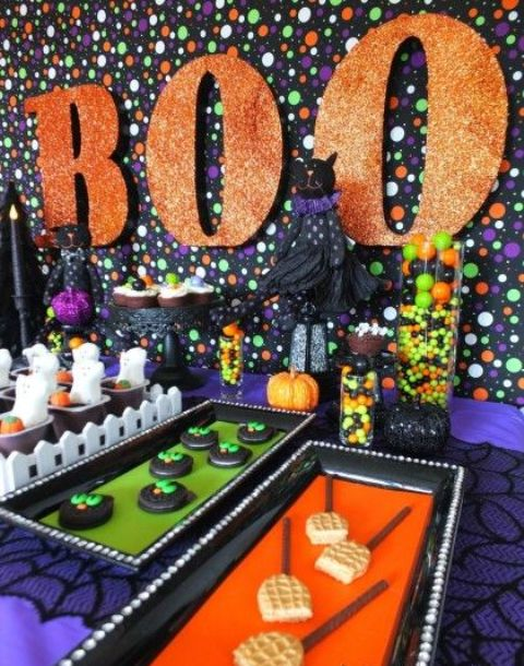 bright Halloween dessert table styling with a polka dot backdrop, orange glitter letters, bold sweets and candies on bold trays for a kids' party